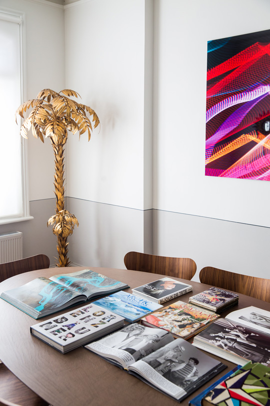 contemporary dinning room table, design magazines and a golden palm tree in the back
