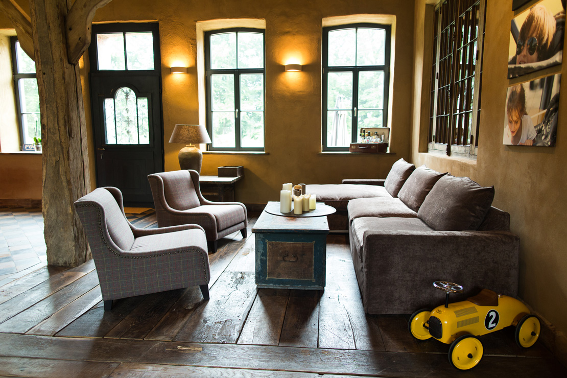 velvet sofa from marie's corner in a cosy and rustic living room