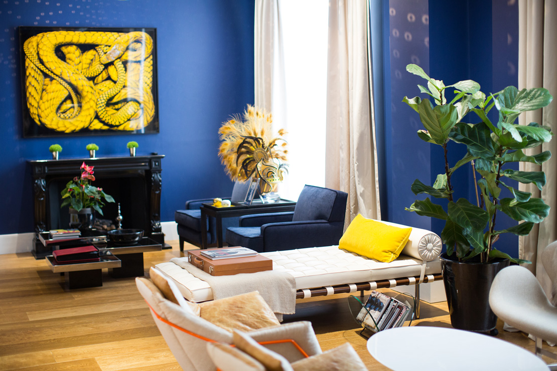 Contemporary modern blue and yellow livingroom with a picture of a yellow snake and  a white sofa