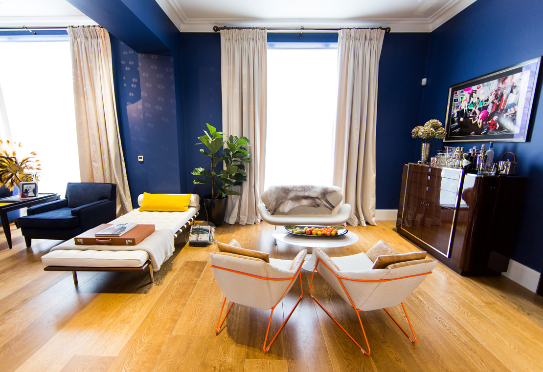 Blue and white living room with exotic wood bar and white armchairs