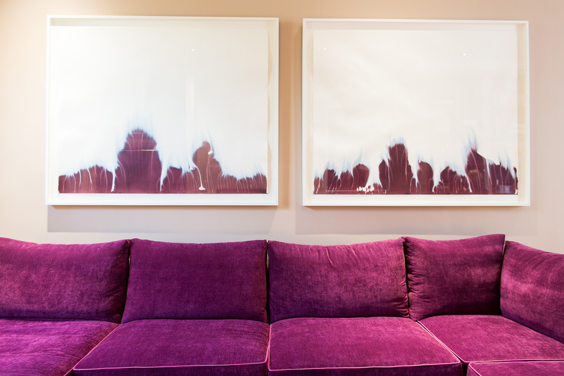 Purple comfortable sofa with purple and white abstract paintings