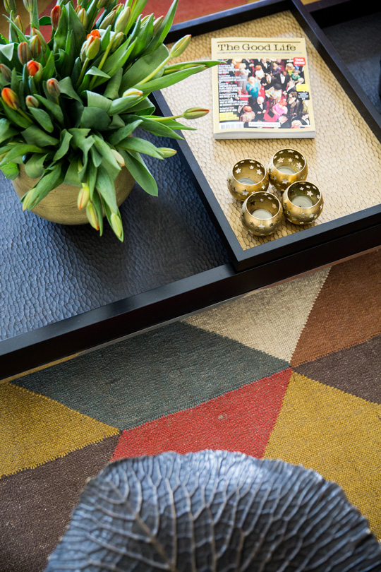 Handcrafted Indian rug with tirangles underneath a living room black coffee table
