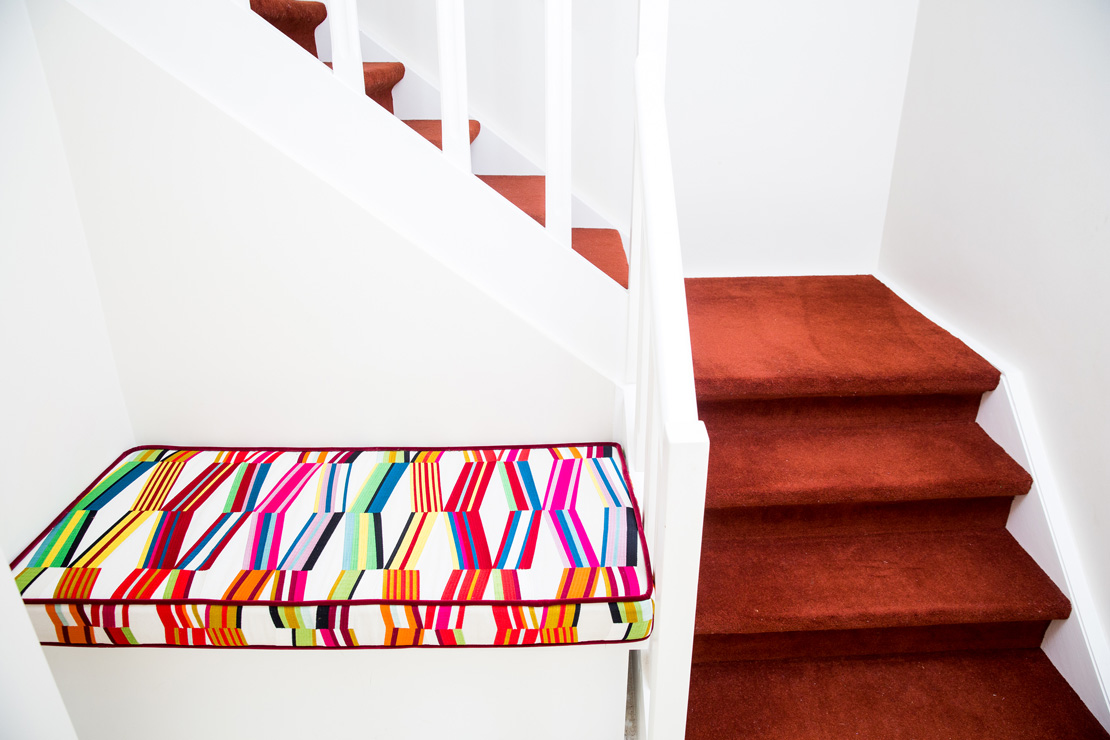 Bench with Fabric from la Maison Pierre Fey next to a white staircase with red carpet