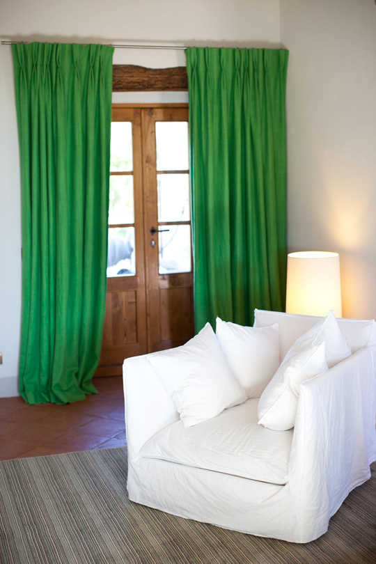 Green linen curtains with a sober white armchair in a tuscany countryhouse
