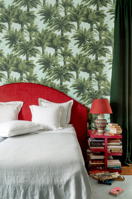 Palm tree wallpaper from pierre frey with red laquered bed table and a headboard by La Maison Pierre frey