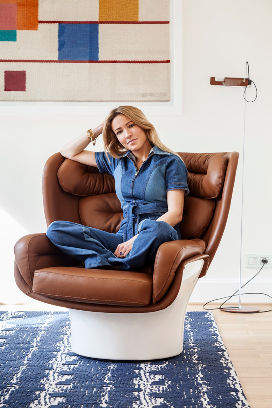 Victoria Maria sitting in a Joe colombo armchair under a swedish tapestry and a spiderlamp from colombo, on a Le Manach rug