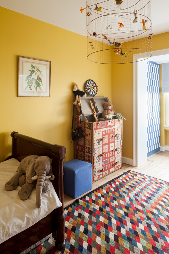 yellow kids bedroom with a kilim chest of drawers from marocco on an iranian carpet and a challieres ceiling lamp with birds