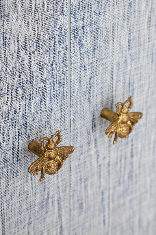 A furniture knob with a Bee on a wardrobe in a blue dressing
