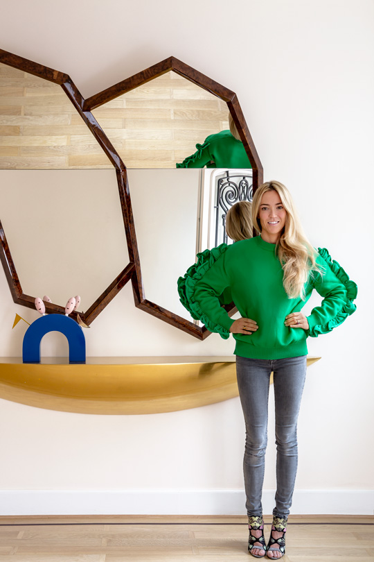 Victoria Maria Geyer Interior Architect standing in front of Portuguese mahogany hanging mirror and Memphis piece of art